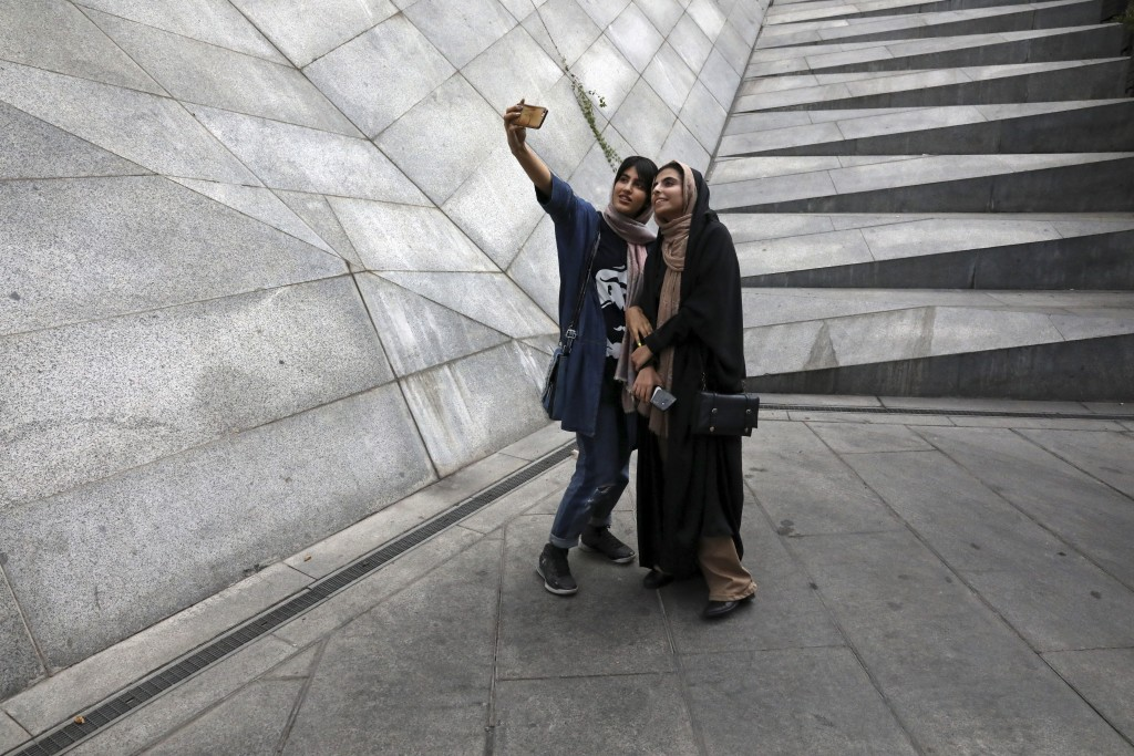 In this Tuesday, July 2, 2019 photo, two Iranian women take selfie outside a shopping mall in northern Tehran, Iran.  A few daring women in Iran's cap