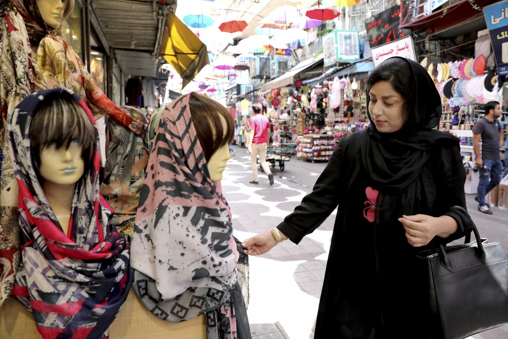 In this Wednesday, July 3, 2019 photo, a woman inspects a headscarf at a market in downtown Tehran, Iran. A few daring women in Iran's capital have be
