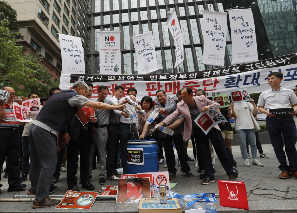 South Korean small and medium-sized business owners pour beers and drinking waters from Japanese brands into a trash can during a rally calling for a ...