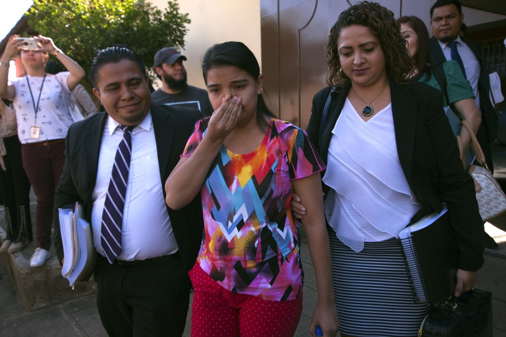 In this Dec. 17, 2018 photo, Imelda Cortez, 20, who was accused of attempting to abort her abuser's baby, walks out of court between her two defense l...