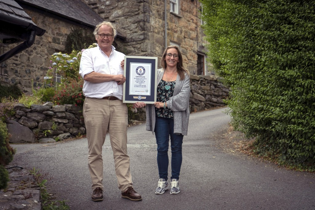 In this undated handout photo provided by Guinness World Records on Tuesday, July 16, 2019, Gwyn Headley and Sarah Badhan, stand on Ffordd Pen Llech w