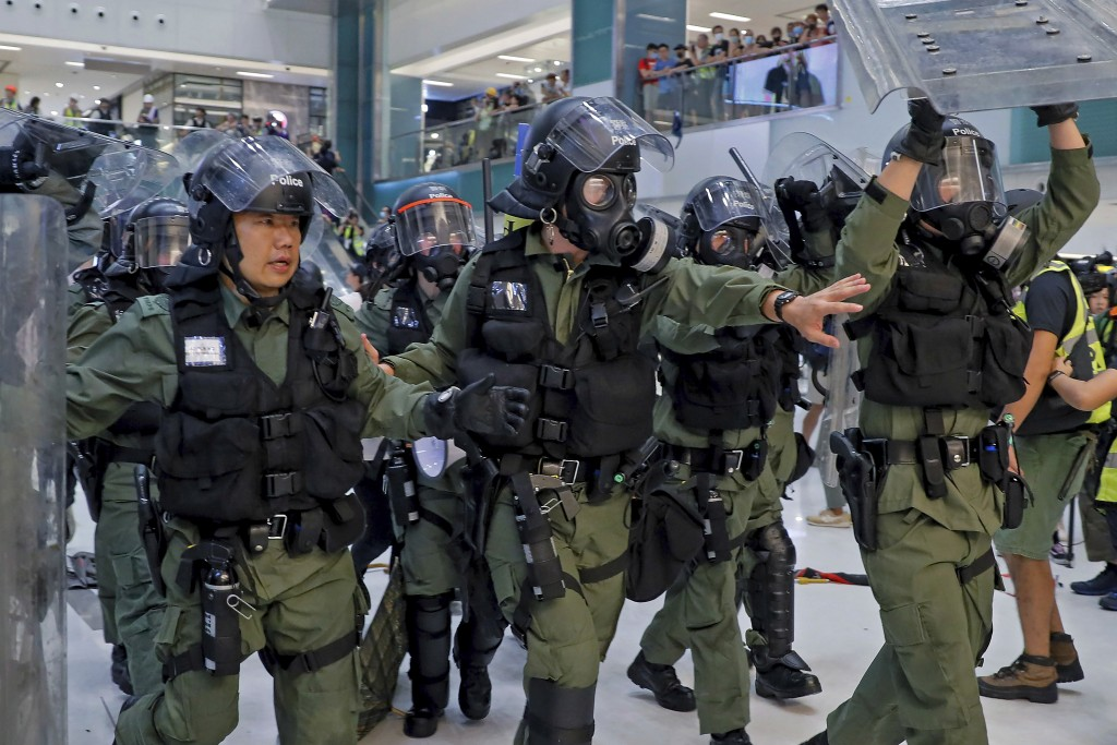 In this Sunday, July 14, 2019, photo, riot policemen move in to disperse the protesters inside a shopping mall in Sha Tin District in Hong Kong. What