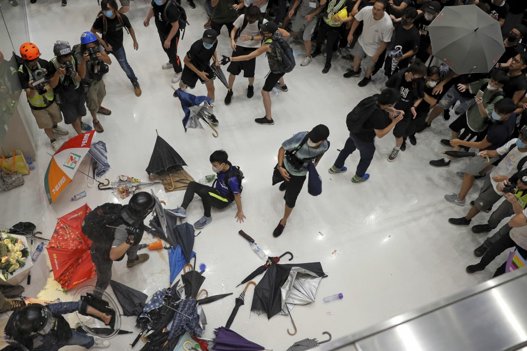 In this Sunday, July 14, 2019, photo, protesters throw umbrellas toward policemen during a crash inside a shopping mall in Sha Tin District in Hong Ko...
