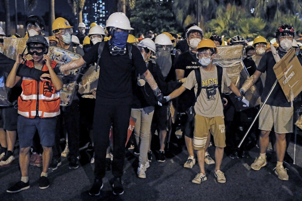 In this Sunday, July 14, 2019, photo, protesters wearing protection gears as they prepare to face-off with policemen on a street in Sha Tin District i