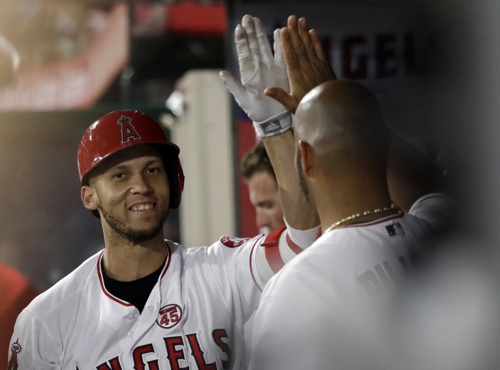 Los Angeles Angels' Andrelton Simmons, left, celebrates his solo home run with teammate Albert Pujols during the third inning of a baseball game again