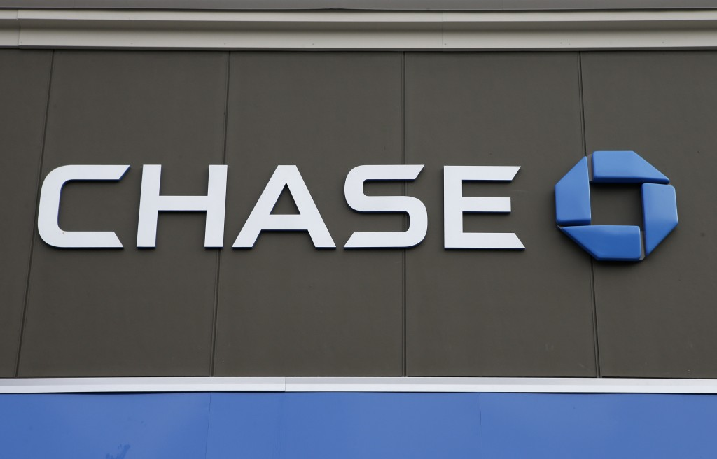 In this Nov. 29, 2018 photo a Chase Bank logo is attached to an exterior wall at a bank location, in Dedham, Mass. JP Morgan Chase reports financial r...