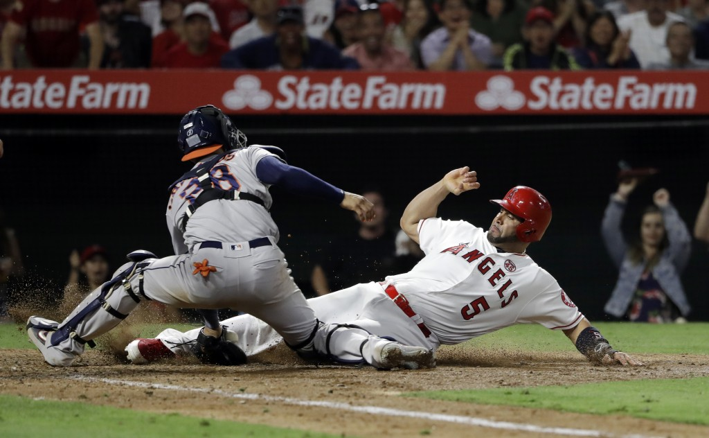 Los Angeles Angels' Albert Pujols, right, scores past Houston Astros catcher Robinson Chirinos after a double by Kevan Smith and a throwing error by A