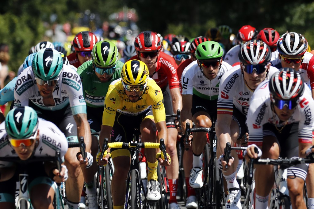 The pack rides with France's Julian Alaphilippe wearing the overall leader's yellow jersey during the tenth stage of the Tour de France cycling race o...