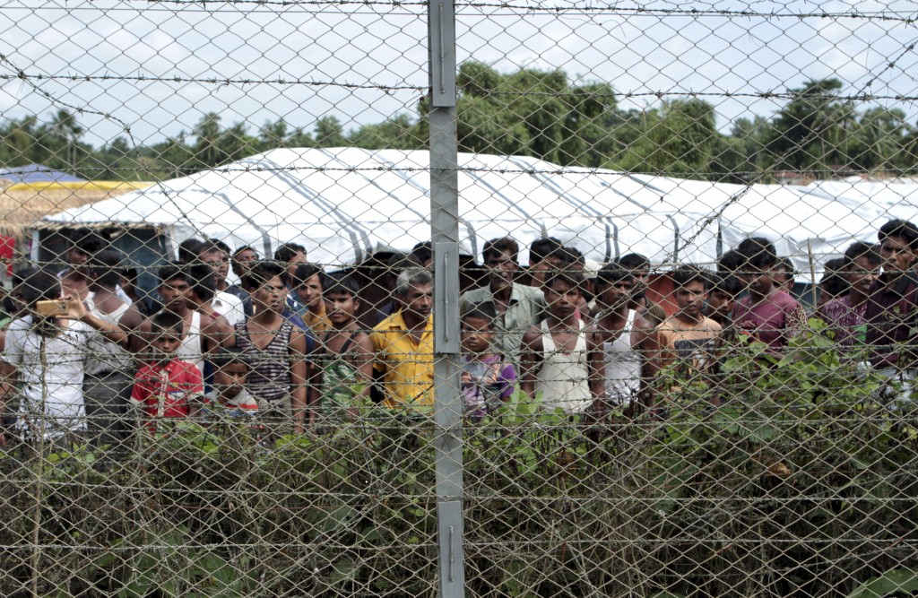 FILE - In this June 29, 2018, file photo, Rohingya refugees gather near a fence during a government organized media tour to a no-man's land between My...