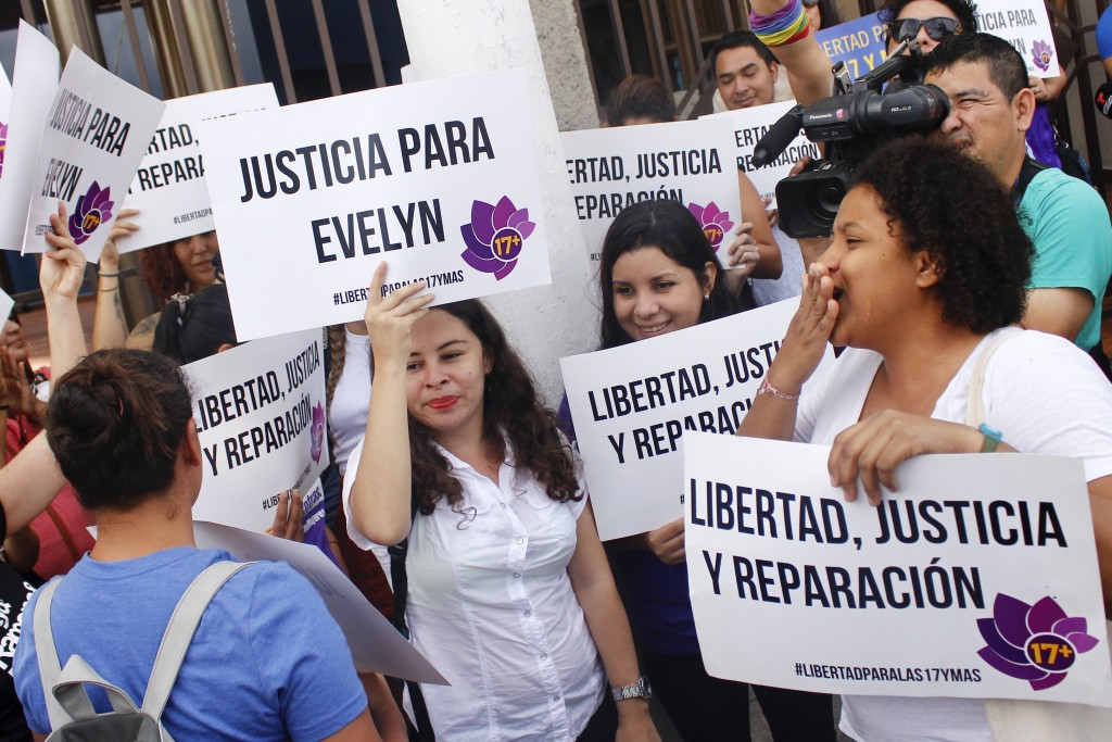 Protestors hold signs calling for justice and freedom for Evelyn Beatriz Hernandez outside the court where she is facing a new trial, after her 30-yea...