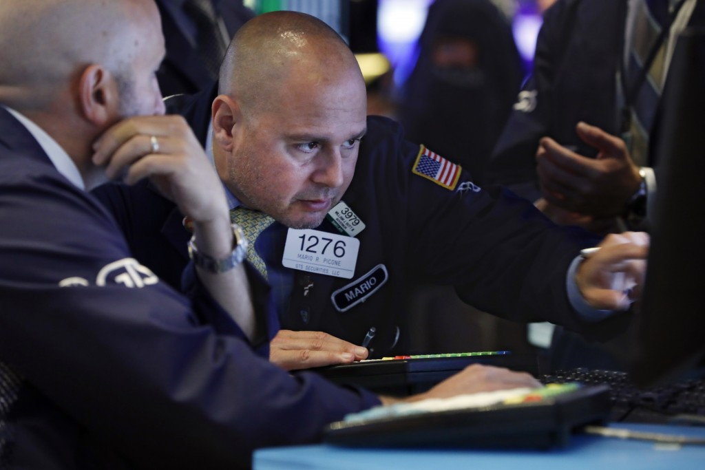 FILE - In this June 18, 2019, file photo specialist Mario Picone, right, works on the floor of the New York Stock Exchange. The U.S. stock market open...