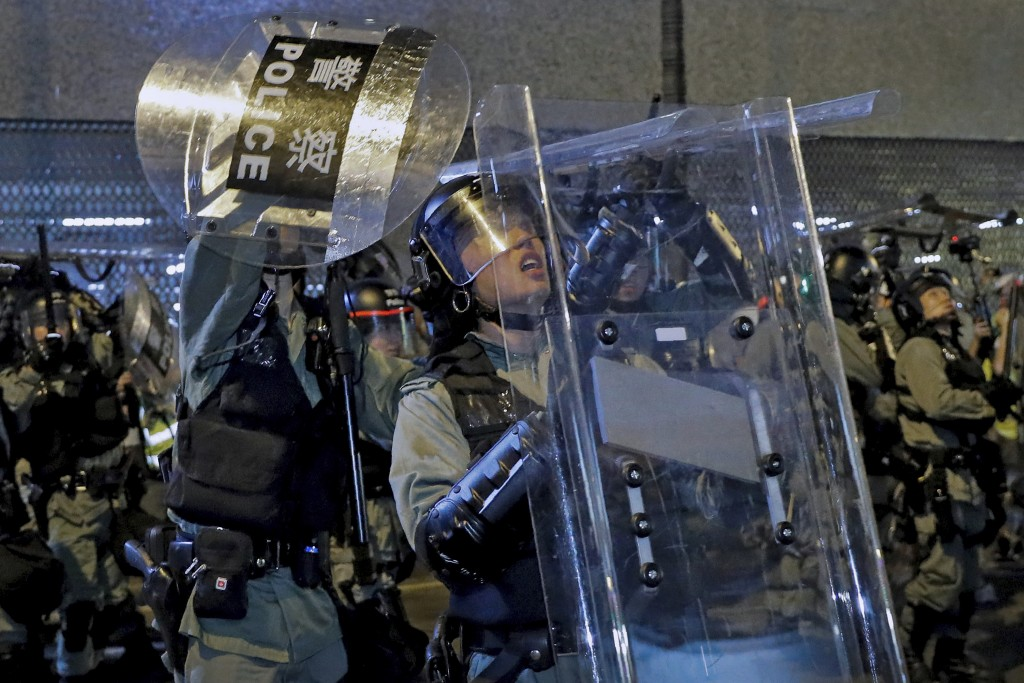 In this Sunday, July 14, 2019, photo, riot policemen use shields to protect themselves from things thrown by protesters during a demonstration in Sha ...