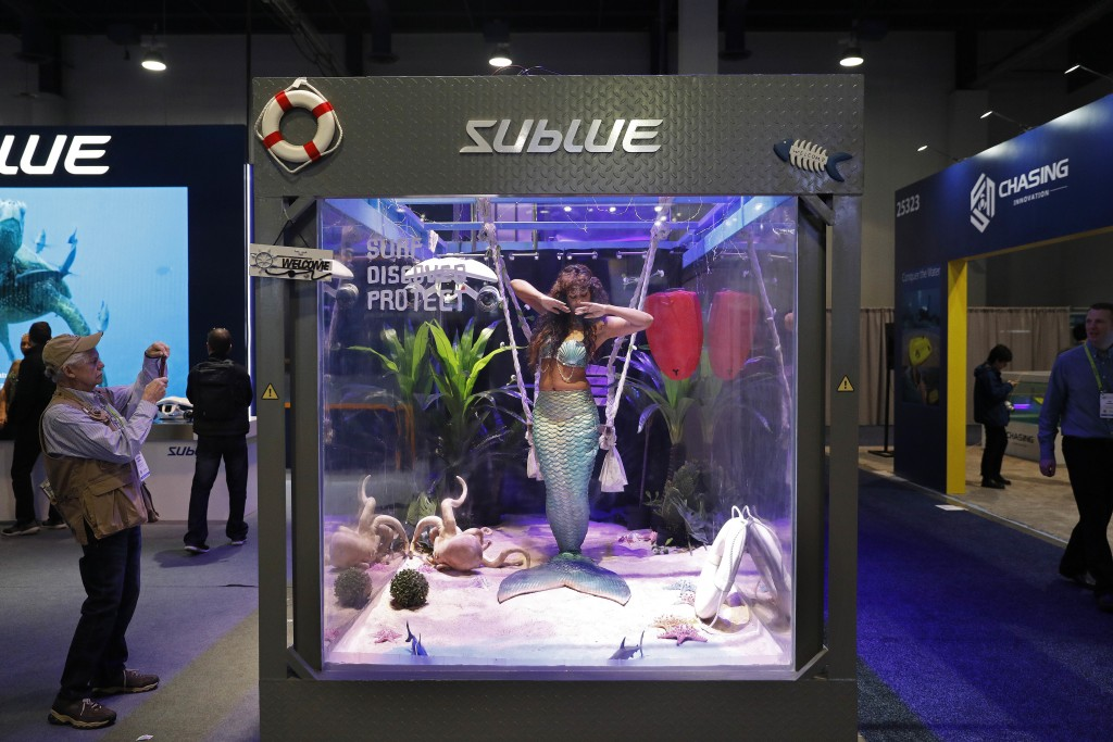 FILE- In this Jan. 9, 2019, file photo a woman dressed as a mermaid performs at the Sublue booth at CES International in Las Vegas. The group that org