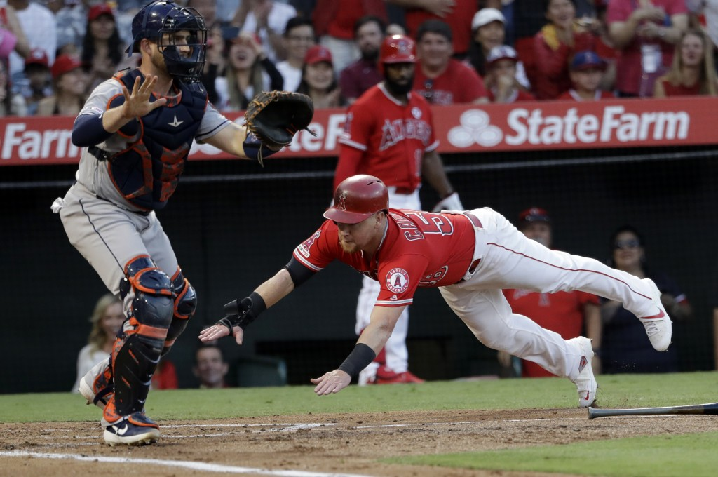 Los Angeles Angels' Kole Calhoun, right, scores past Houston Astros catcher Max Stassi on a three-run double by Albert Pujols during the first inning