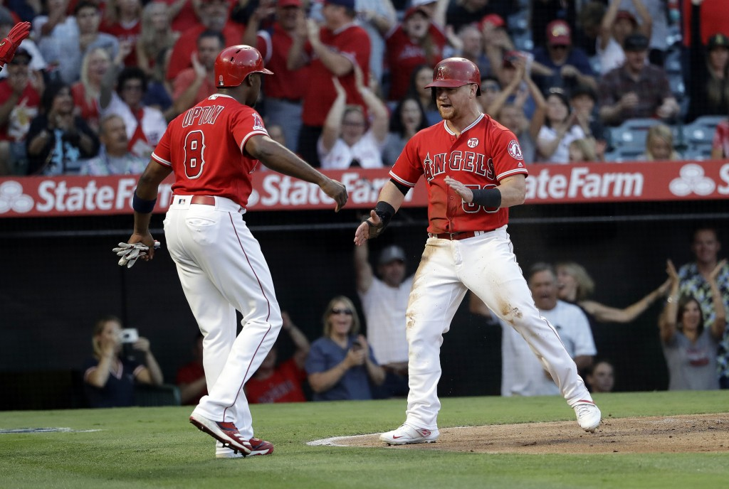 Los Angeles Angels' Kole Calhoun, right, celebrates with Justin Upton (8) after they scored on a double by Albert Pujols during the first inning of a ...