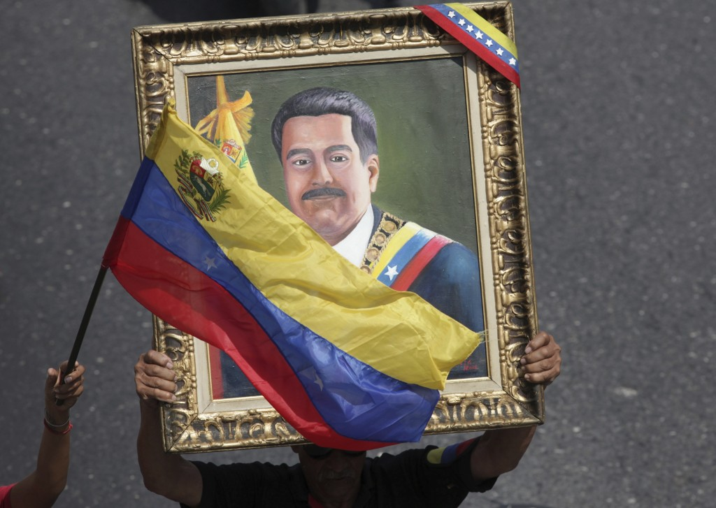 FILE - This May 1, 2019 file photo shows a government supporter holding a framed image of Venezuelan President Nicolas Maduro during an anti-imperiali...