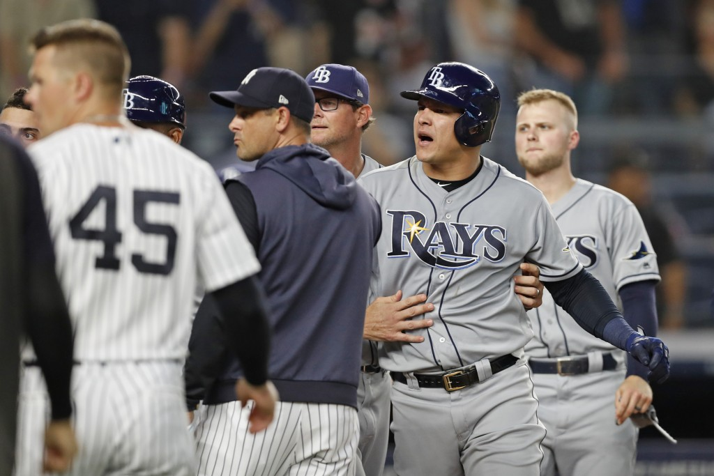 Tampa Bay Rays pitching coach Kyle Snyder, center rear, restrains Rays' Avisail Garcia, second from right, as benches and bullpens cleared during a di...