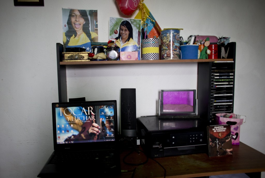 A laptop and pictures of Karen Palacios stand on her desk at her house in Los Teques in the outskirts of Caracas, Venezuela, Tuesday, July 16, 2019. K...