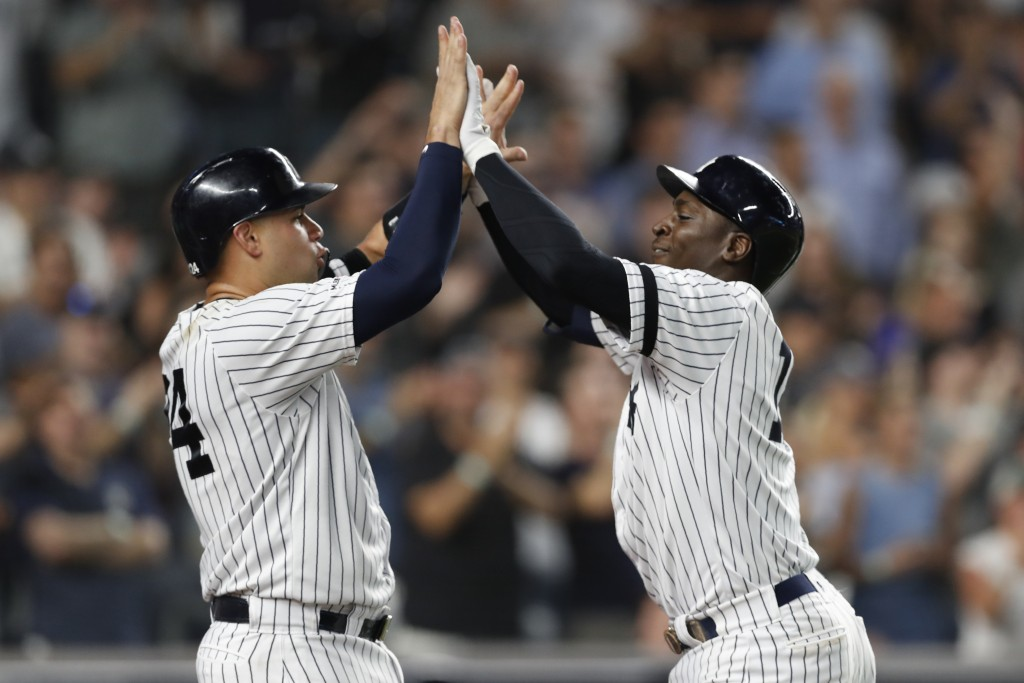New York Yankees' Gary Sanchez, left, congratulates Didi Gregorius after scoring on Gregorius' grand slam during the eighth inning of the team's baseb...