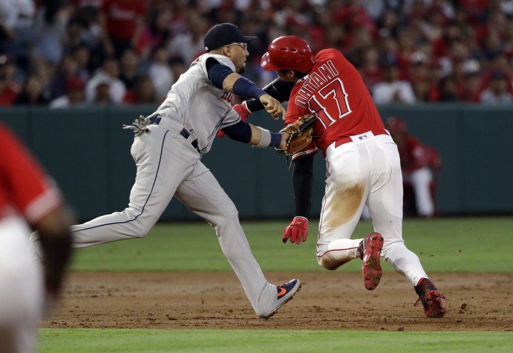 Los Angeles Angels' Shohei Ohtani (17) is tagged out by Houston Astros third baseman Yuli Gurriel on a rundown between second and third base following...
