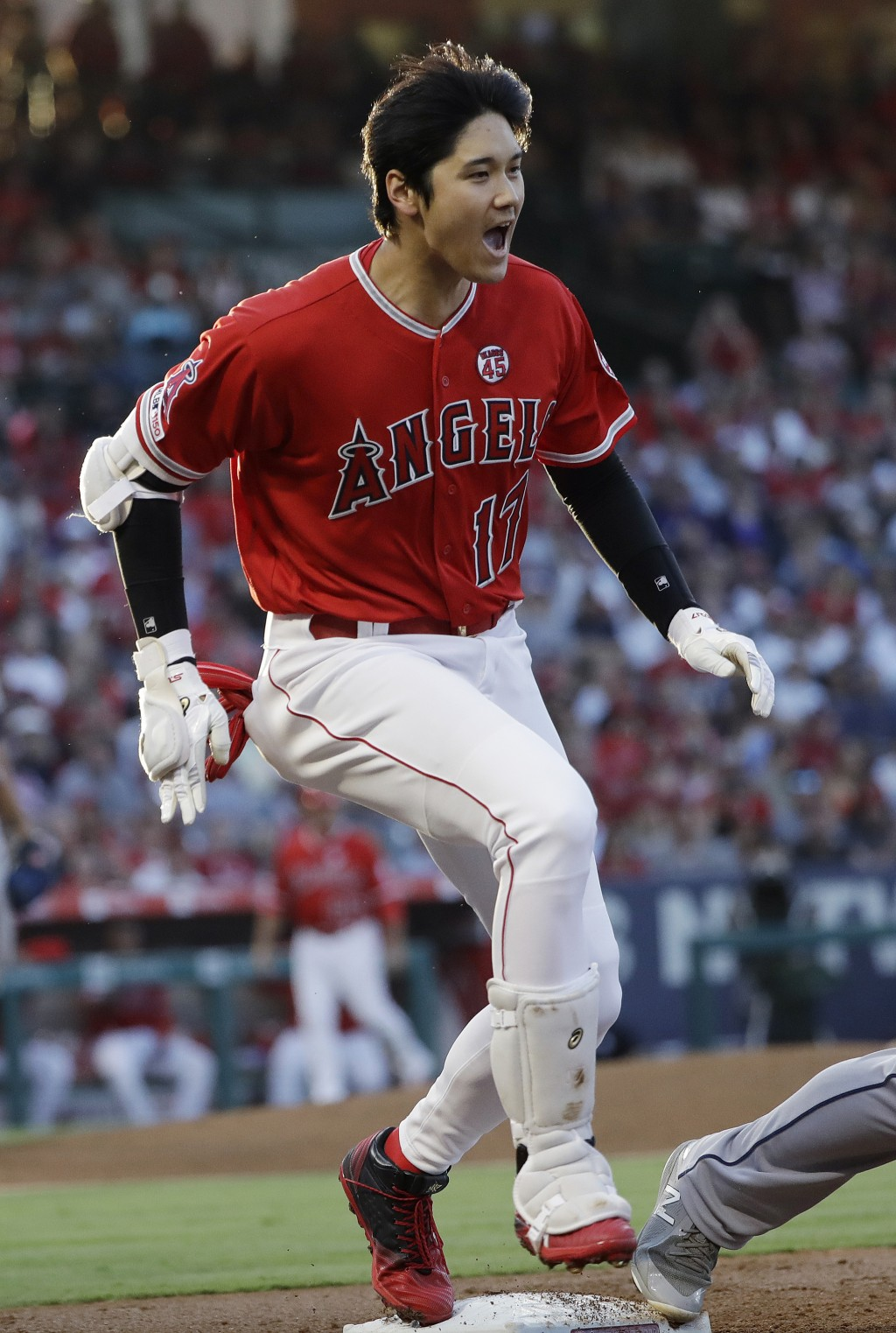 Los Angeles Angels' Shohei Ohtani reaches first base with an RBI infield single against the Houston Astros during the first inning of a baseball game ...