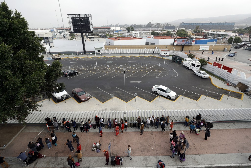 Migrants line up along an entrance to the border crossing as they wait to apply for asylum in the United States, Tuesday, July 16, 2019, in Tijuana, M...