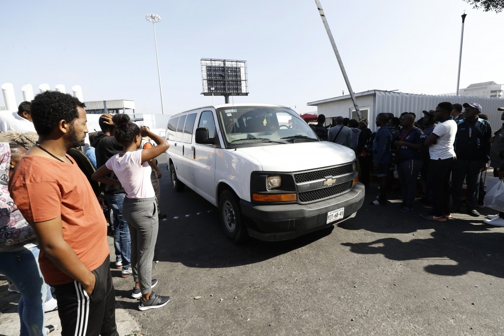 A van carrying migrants on their way to apply for asylum in the United States passes a group of migrants still awaiting a chance to apply on the borde...