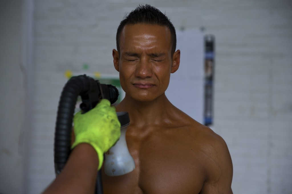 In this July 14, 2019 photo, Mexican bodybuilder Carlos Suarez is coated with spray tanner as he prepares to perform an exhibition routine as training