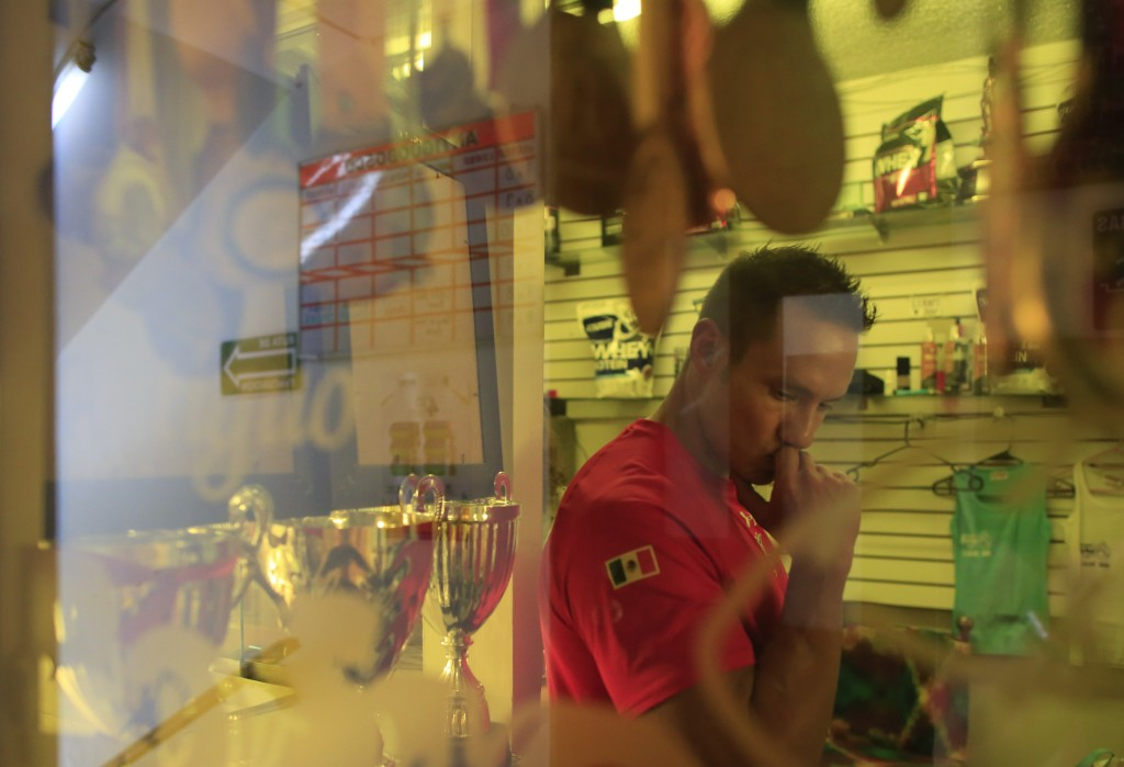 In this June 6, 2019 photo, Carlos Suarez is seen past his bodybuilding medals and trophies as he stands inside the glass-encased office at the neighb...