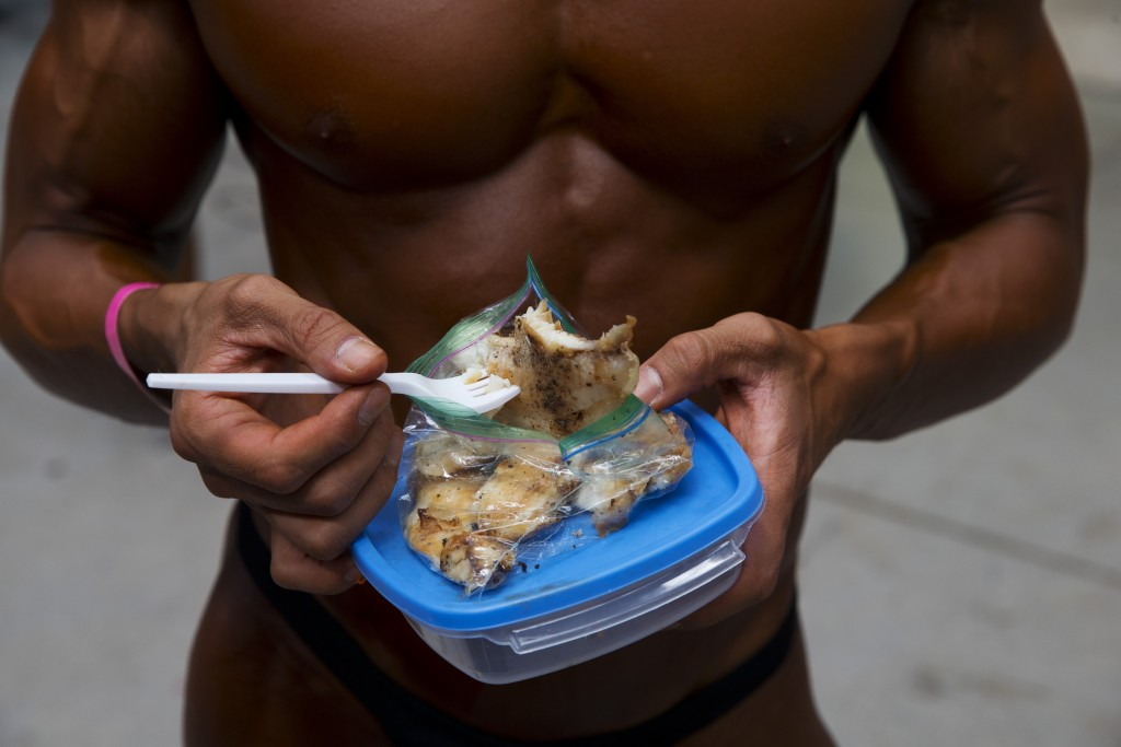 In this July 14, 2019 photo, Mexican bodybuilder Carlos Suarez eats lunch before performing an exhibition routine as training to handle the pressure o...