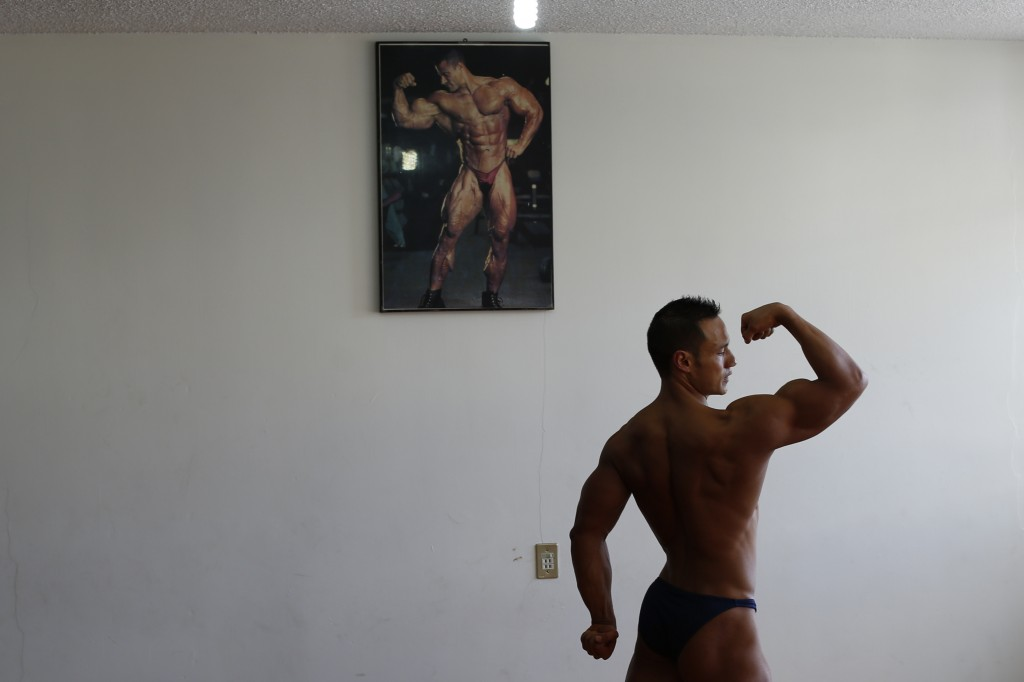 In this June 6, 2019 photo, Carlos Suarez practices his bodybuilding poses as part of his daily training regimen ahead of the Pan Am Games, at the nei