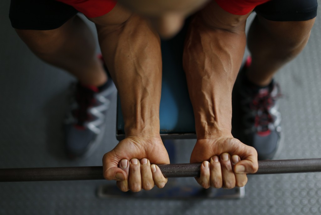 In this June 6, 2019 photo, Mexican bodybuilder Carlos Suarez does forearm curls as part of his daily training regimen ahead of the Pan Am Games, at t