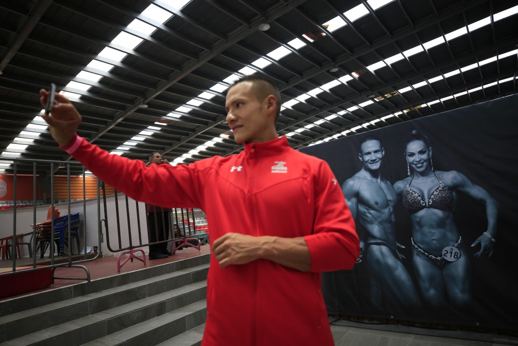 In this July 14, 2019 photo, Mexican bodybuilder Carlos Suarez takes a selfie in front of a sign showing a picture of him and Xyomara Valdivia, Mexico