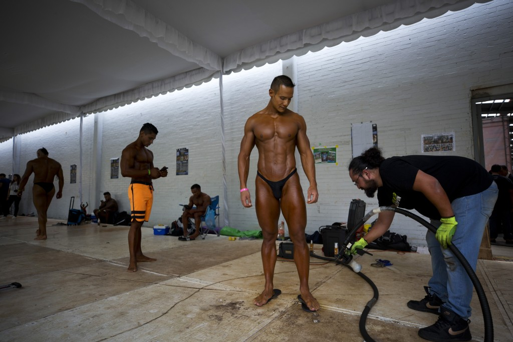 In this July 14, 2019 photo, Mexican bodybuilder Carlos Suarez is coated with spray tanner before performing an exhibition routine as training to hand...