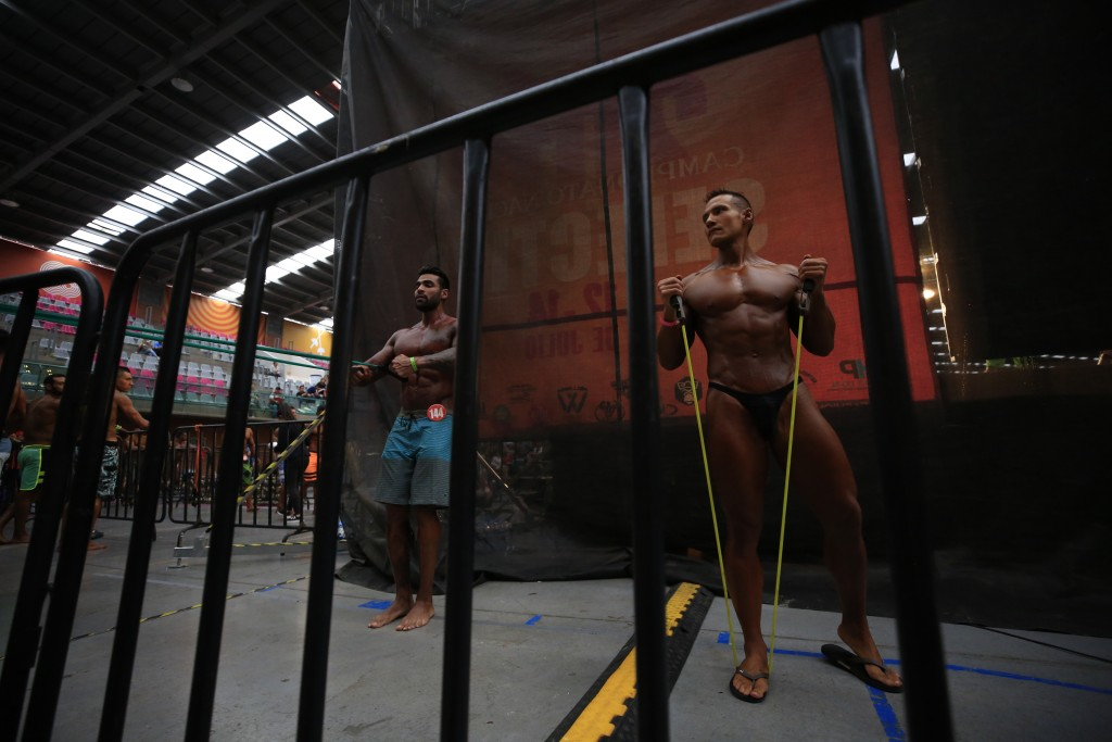 In this July 14, 2019 photo, Mexican bodybuilder Carlos Suarez, right, works out with a resistance band before performing an exhibition routine as tra...
