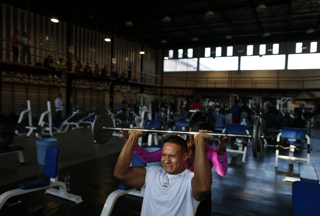 In this June 9, 2019 photo, Mexican bodybuilder Carlos Suarez trains for the upcoming Pan Am Games with Martha Elizabeth Sanchez, a former champion bo