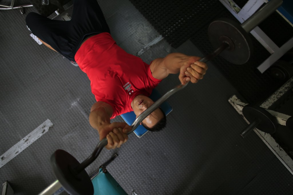 In this June 6, 2019 photo, Carlos Suarez lifts weights as part of his daily training regimen ahead of the Pan Am Games, at the neighborhood gym owned