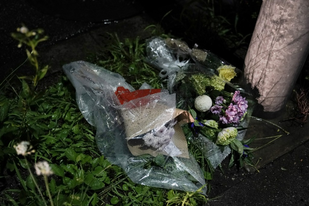 Flowers are placed near the Kyoto Animation building destroyed in an arson attack Thursday, July 18, 2019, in Kyoto, Japan.  The blaze started in the ...