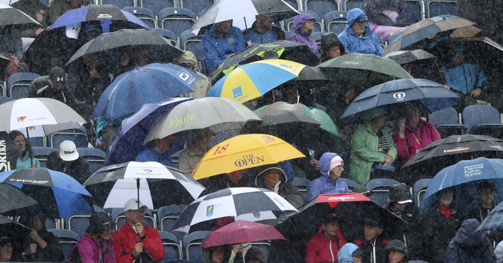 Spectators take cover under umbrellas a heavy rain falls as they watch golfers during the first round of the British Open Golf Championships at Royal ...