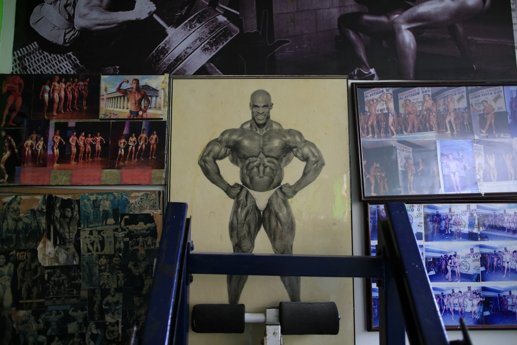 In this June 6, 2019 photo, pictures of bodybuilders decorate the walls at the neighborhood gym, owned by his parents, where Carlos Suarez trains for