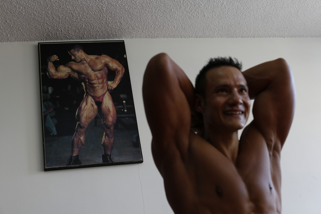 In this June 6, 2019 photo, Carlos Suarez practices his bodybuilding poses as part of his daily training regimen ahead of the Pan Am Games, at the nei...