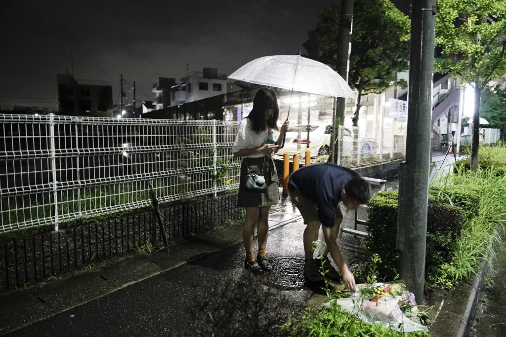 A couple places flowers near the Kyoto Animation building, Friday, July 19, 2019, background left, that was destroyed in an arson attack in Kyoto, Jap...