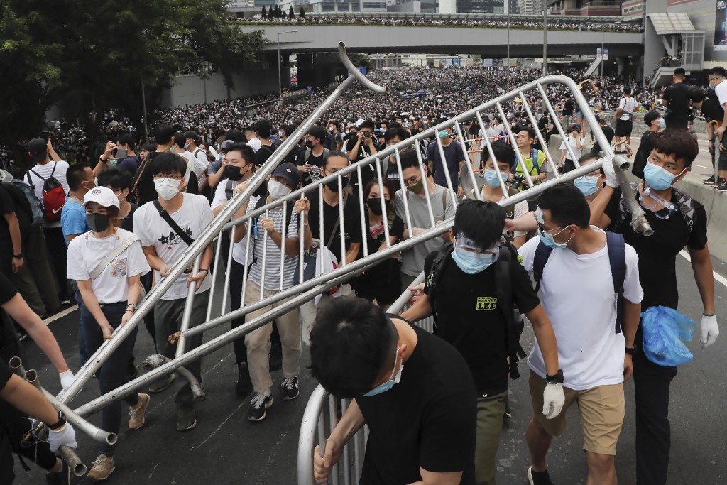 FILE - In this Wednesday, June 12, 2019, file photo, protesters carry barricades as they march toward the Legislative Council in Hong Kong. Hundreds o