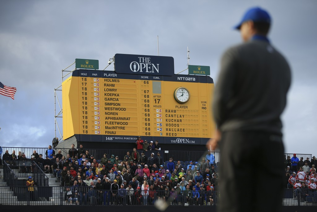Tiger Woods of the United States prepares to chip onto the 18th green, as the scoreboard shows the leading players and Woods score been at bottom left...
