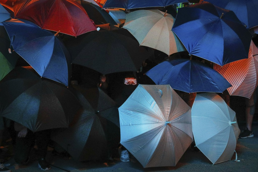 In this Sunday, July 7, 2019, photo, protesters use umbrellas as a shield as they face police officers on a street in Hong Kong. If yellow umbrellas w