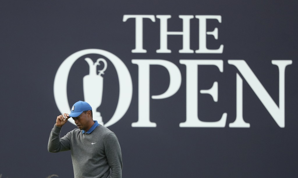 Tiger Woods of the United States tips his hat as he completes his first round of the British Open Golf Championships on the 18th green at Royal Portru...