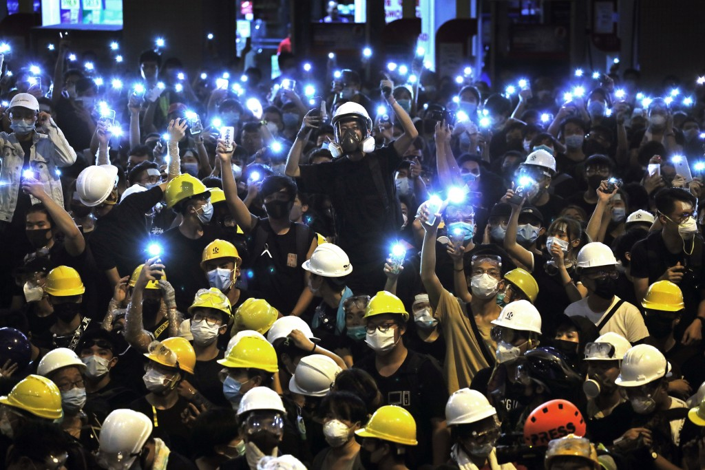 FILE - In the Friday, June 21, 2019, file photo, protesters wearing yellow hardhats hold up mobile phone lights in front of police headquarters in Hon