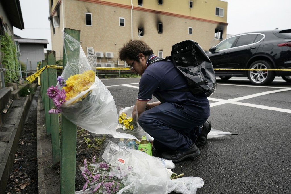 A man places flowers outside the Kyoto Animation Studio building consumed in an arson attack, Friday, July 19, 2019, in Kyoto, Japan. A man screaming ...