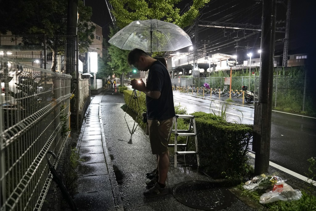"""A couple prays after placing flowers near the Kyoto Animation building, Friday, July 18, 2019, in Kyoto, Japan.   A man screaming """"You die!"""" burst int..."""