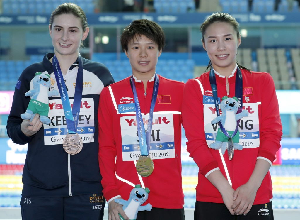 Gold medalist China's Shi Tingmao, centre, stands with silver medalist and compatriot Wang Han, right, and bronze medalist Australia's Maddison Keeney...